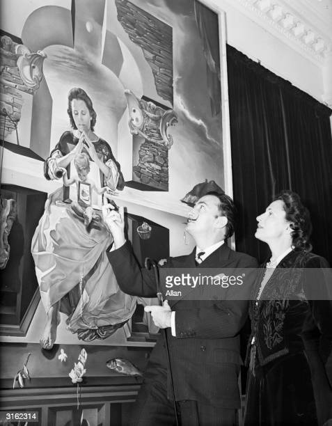 Spanish artist Salvador Dali and his wife Gala looking at one of his paintings entitled 'The Madonna of Port Lligat' Gala herself modelled for the...