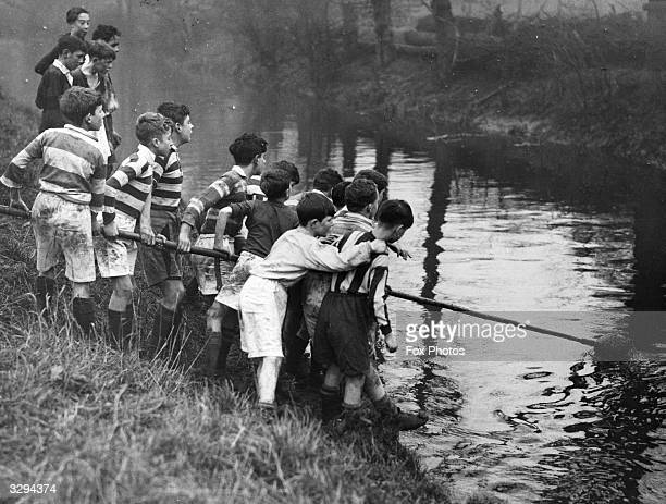 Boys of West Ham Secondary and The Baines Foundation school are united in retrieving the ball from the river during their match at Leytonstone Rugby...