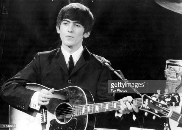 Guitarist and singer George Harrison of the popular Merseybeat group The Beatles performing during a live concert