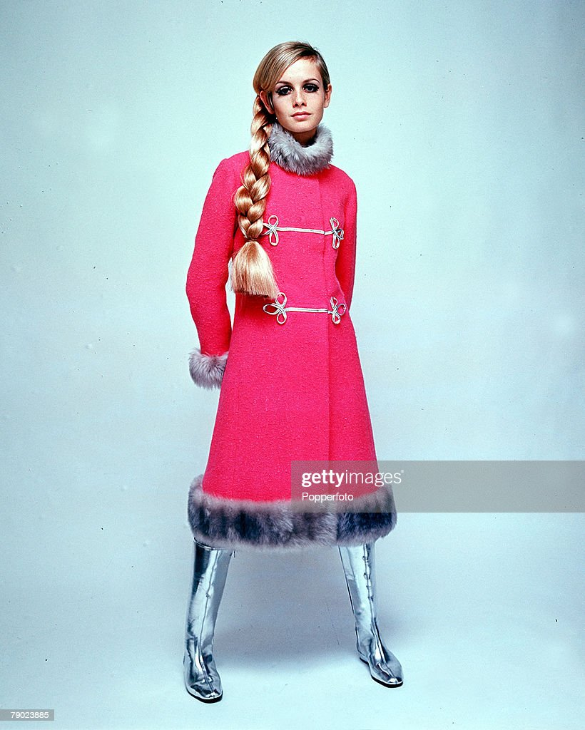 3rd December 1966, Modelling, A picture of British model Twiggy wearing a fashionable pink full length coat with fur trimming, silver boots, and her hair plaited