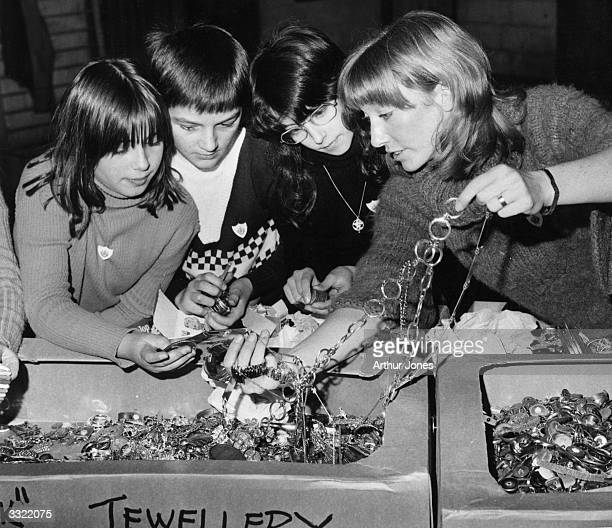 Lesley Judd a presenter of the children's programme 'Blue Peter' sorting out a box of jewellery with the help of some children in the 'Blue Peter...
