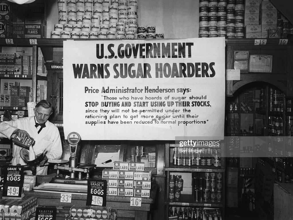 An A & P grocery store displays a sign that reads, 'US Government Warns Sugar Hoarders' to support the rationing effort, New York City, World War II.