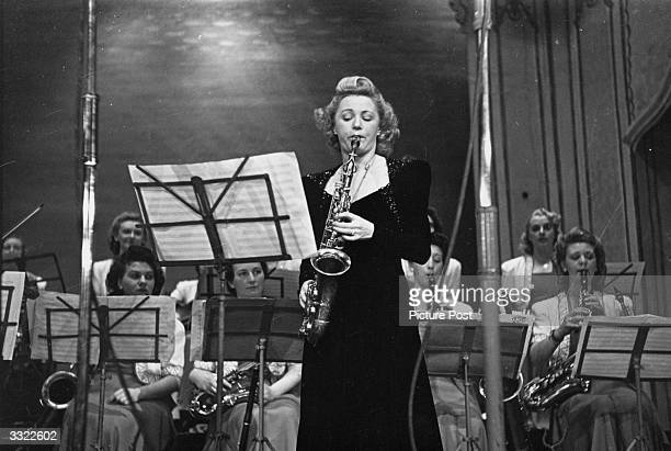 British alto saxophonist and band leader Ivy Benson, soloing on stage, backed by her band the Ladies Dance Orchestra. Original Publication: Picture...