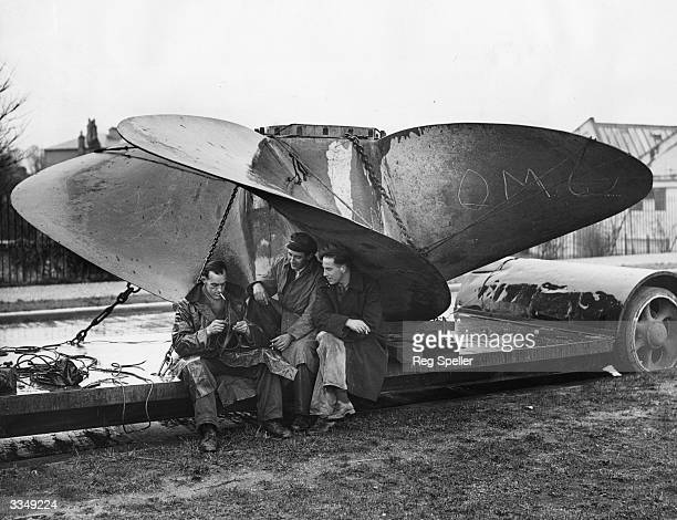 Workmen sheltering from the rain beneath the RMS Queen Mary's 30ton propeller which is being transported from Southampton to Deptford for repairs