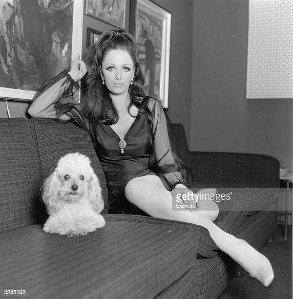 Writer and actress Jackie Collins at home with her pet poodle