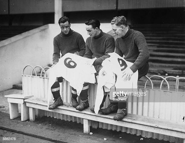 Three Tottenham Hotspur FC soccer players looking at their new numbered football shirts for the third round FA cup tie against Watford at White Hart...