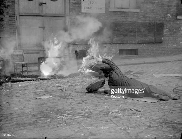 A member of the ARP shows prospective Firewatchers how to put out burning furniture with a stirrup pump