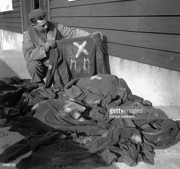 An American soldier examining the painted clothing of slaves outside one of the factory workshops of Struthof 'DeathFactory' concentration camp near...