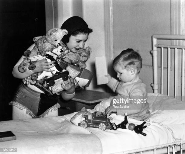 Dancer Alma Jones currently appearing in 'A Night In Venice' at the Cambridge Theatre gives a young patient some Christmas presents during a visit...
