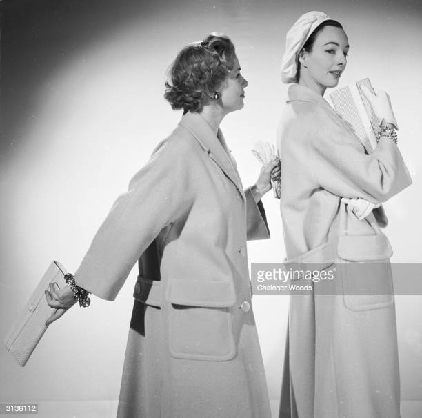 Two models wear loose fitting coats with raglan sleeves large patch pockets at hip level and half belts and carry clutch bags One wears a loose beret...