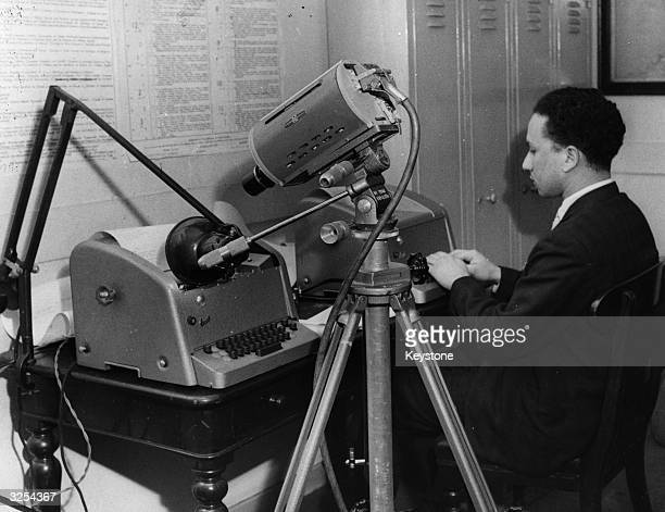 A TV camera trained on a teleprinter as the operator types the details of train arrivals and departures The information is then relayed to a screen...