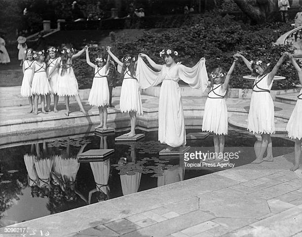 Dancers in 'grecian' costume stand on stepping stones across a lily pond at a Hampstead Garden Fete