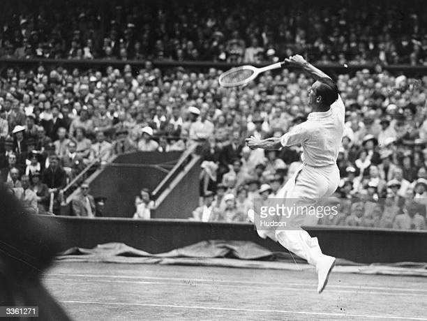 British tennis player Fred Perry in action against Gottfried von Cramm of Germany during the Men's Singles Final of the Wimbledon Lawn Tennis...