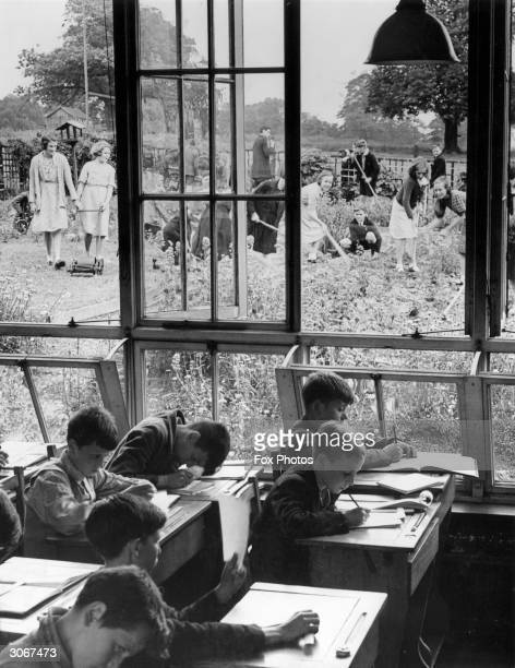 Some pupils at South Featherstone Modern School, Purston, Yorkshire have their heads down over their desks while others are busy in one of the...