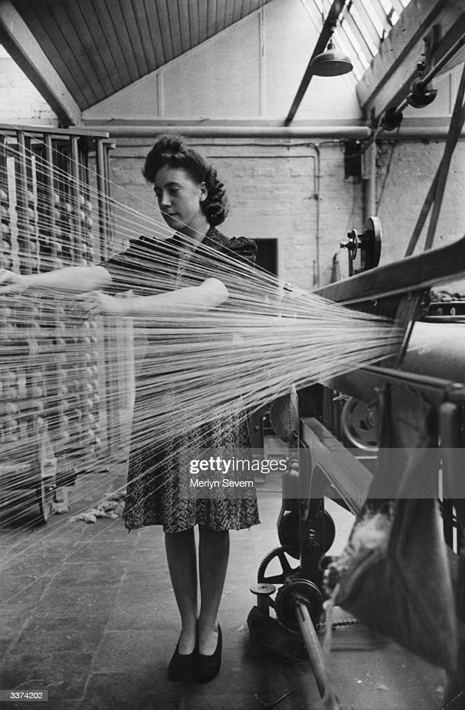 A female textile worker at work in a linen mill's doubling room