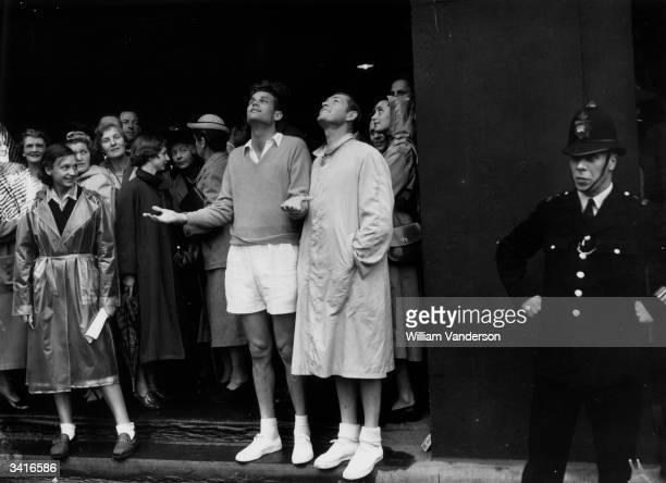 American tennis player Gardnar Mulloy looking up at the rainy skies at Wimbledon.