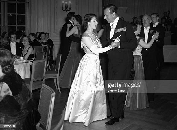 Princess Elizabeth dances with Lord Louis Mountbatten during a fundraising dinner at the Savoy Hotel in London