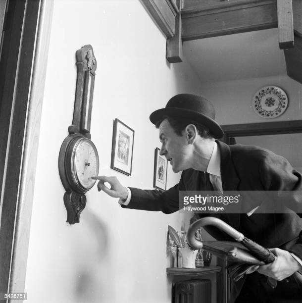 A businessman checks the weather forecast on his barometer before setting out for work Rain seems to be on the cards as he decides to take his...