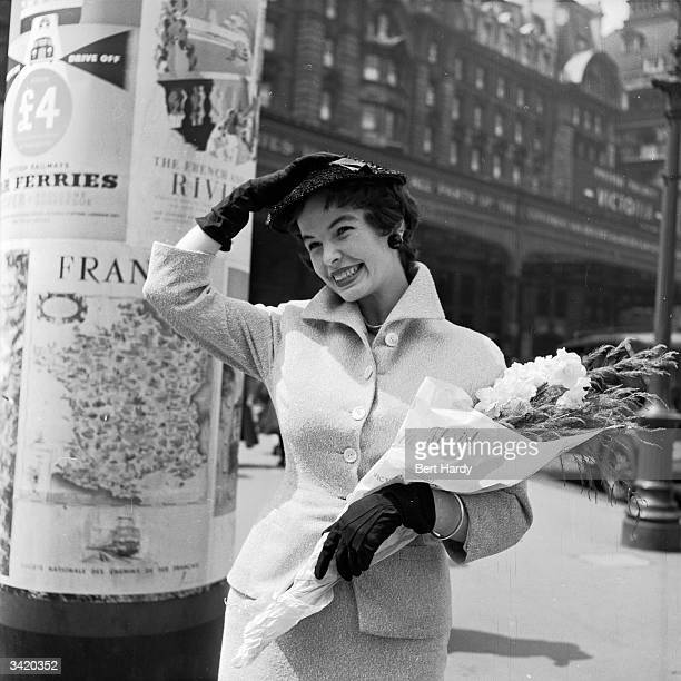 Secretary Janet Jones training for a career in modelling poses with a bouquet of flowers in her arms outside Victoria train station in London...