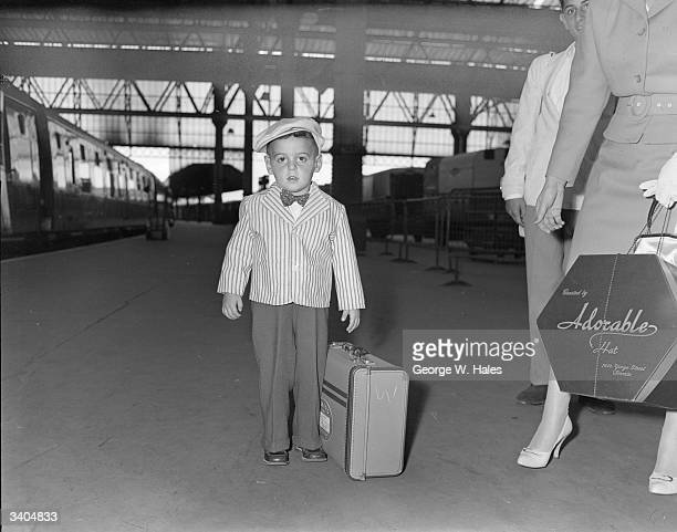 Three year old Mark Sheffer of Toronto with his luggage as he leaves the boat train at Waterloo London He travelled to England on the Holland America...