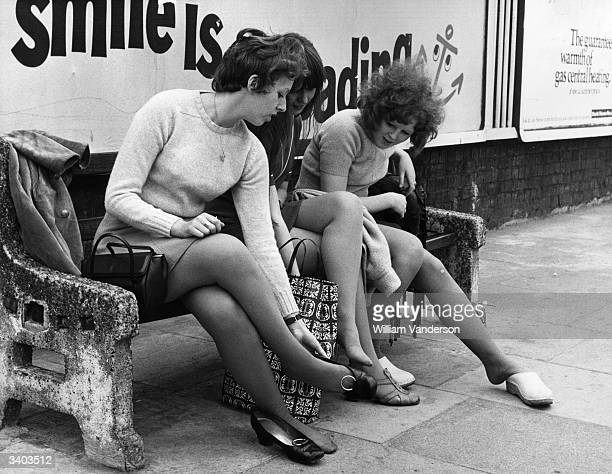 Footsore office girls rest their weary feet in Bow East London as they make their way to work during a oneday strike by Underground signalmen