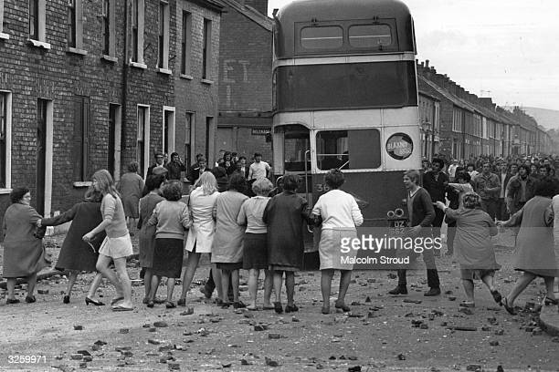 A commandeered bus is driven backwards through a picket of women who want the violence to end during riots on the Falls Road Belfast