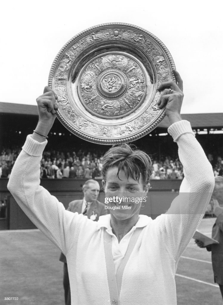 Margaret Court (nee Smith) of Australia holds the Wimbledon women's singles trophy above her head after beating Billie Jean King in the final.