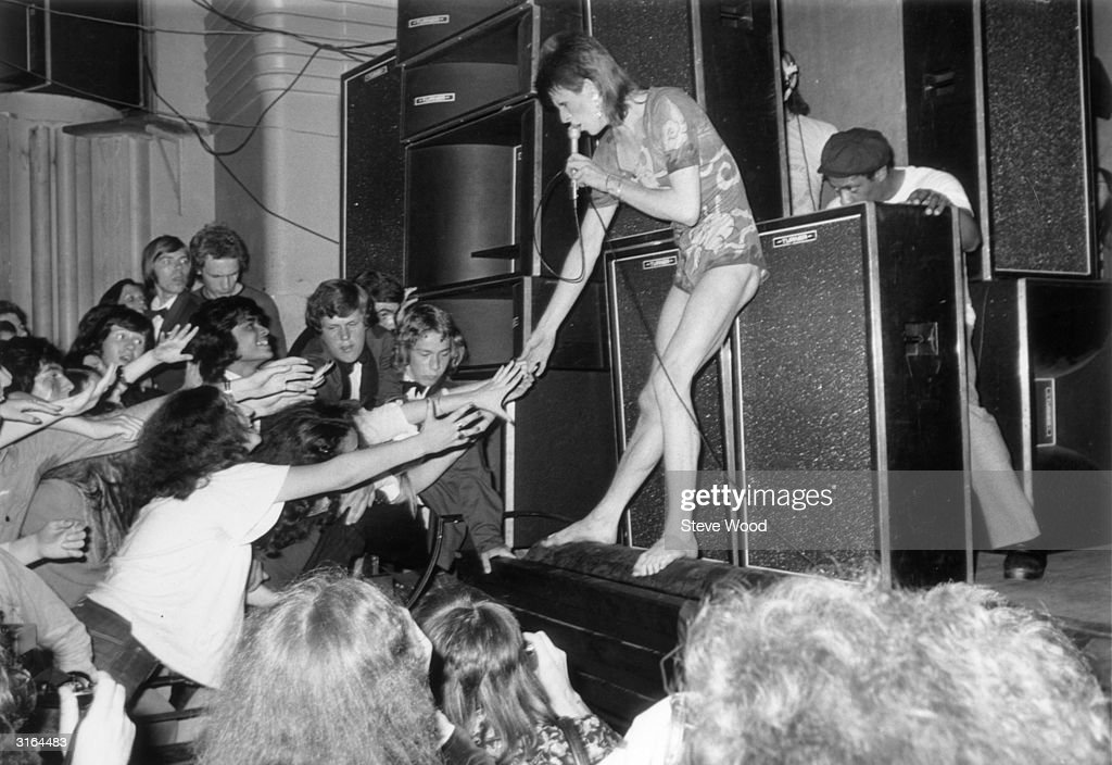Adoring fans reaching out to touch the hand of the English pop star, David Bowie, during the concert at the Hammersmith Odeon where Bowie announced that he was retiring his alter-ego 'Ziggy Stardust'.