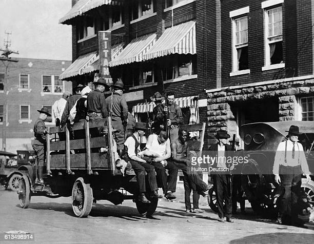 "Injured and wounded men are being taken to hospital by National guardsmen after racially motivated riots, also known as the ""Tulsa Race Massacre"",..."