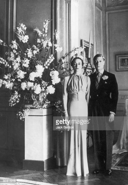 Fulllength portrait of the Duke of Windsor and Wallis Warfield posing next to a floral arrangement after their wedding in the Chateau de Conde near...