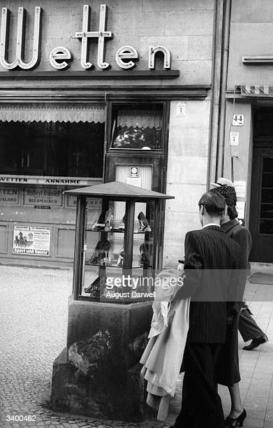 A glass showcase in the middle of a Berlin street displaying some of the wares of a nearby shop Original Publication Picture Post 152 Berlin On A...