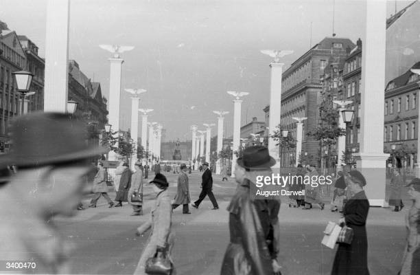 Crowds on the Berlin boulevard of Unter Den Linden The lime trees which gave the avenue its name were cut down to make way for rows of plywood eagles...