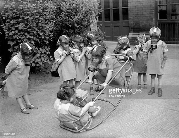 Nursery school children at play wearing gas masks during World War II