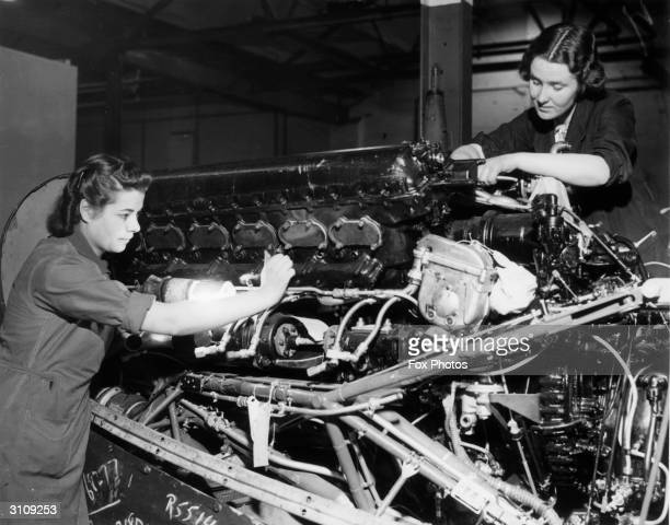 Attache case maker Doris Tampling and domestic servant Sylvia Hall dismantle the engine of a Lancaster aircraft.