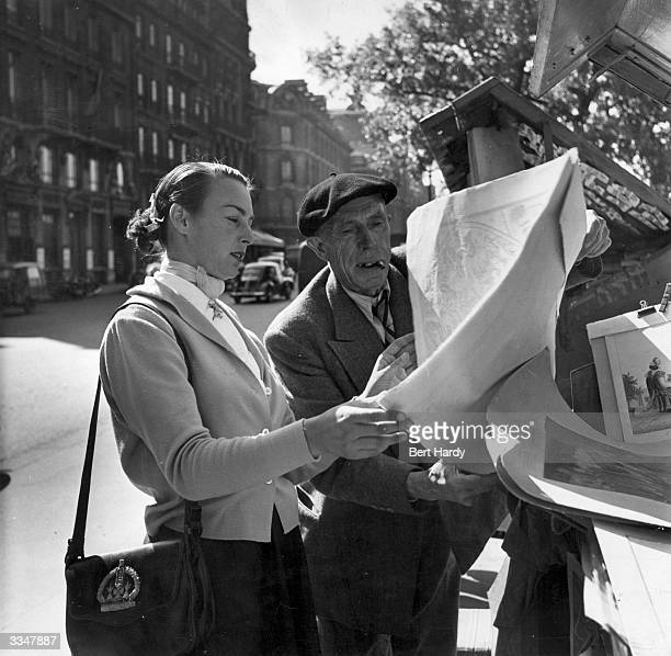 American tennis player Gertrude Moran or Gorgeous Gussie examines an old map at a stall on the Quai Voltaire during a sightseeing tour of Paris...