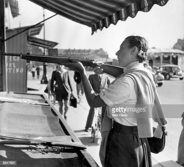 American tennis player Gertrude Moran or Gorgeous Gussie tries her hand at a shooting stall at a fair near les Invalides in Paris Original...