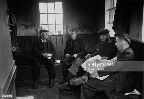 Johnnie McGuirl 2nd left a railway worker who earns an average of 4 15s 6d a week takes a break for a cup of tea with other members of his gang He...