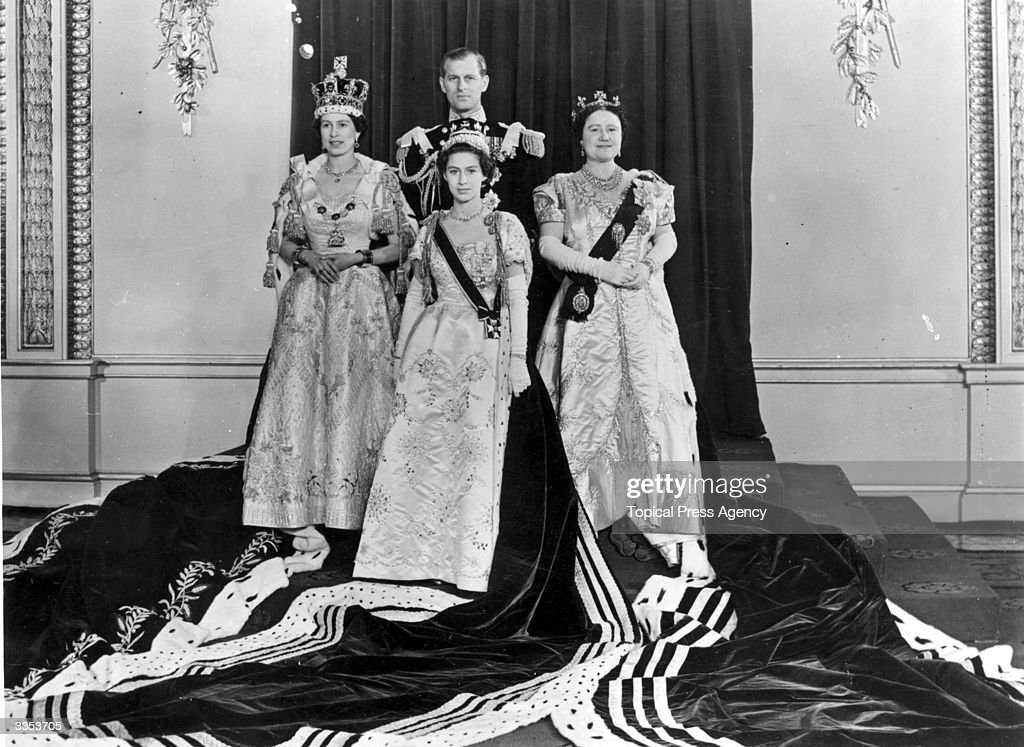 Queen Elizabeth II (left) with Philip, Duke of Edinburgh, Princess Margaret Rose (1930 - 2002) and Queen Elizabeth The Queen Mother (right) wearing full Coronation regalia in the Throne Room of Buckingham palace after her Coronation ceremony.