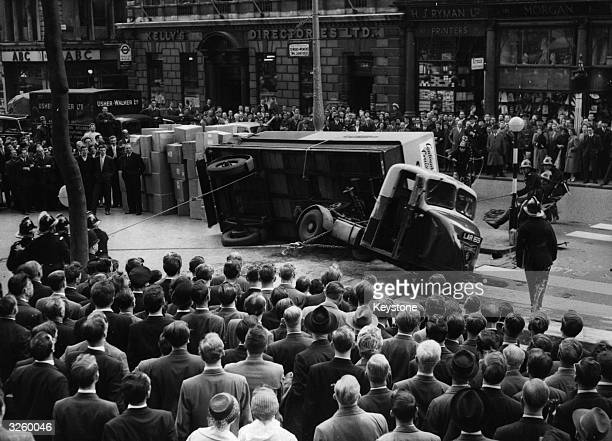A British Rail Parcel truck overturns in the Strand London bringing traffic to a standstill Firemen using winches attempt to turn it upright again