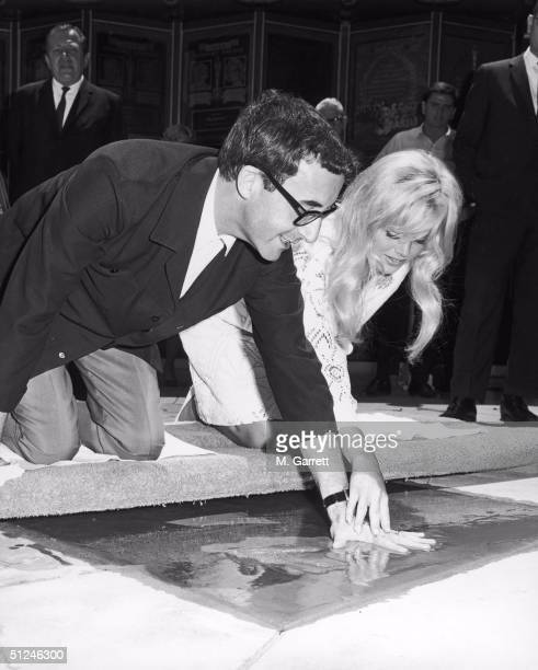 3rd June 1964, British actor Peter Sellers is helped by his wife, Swedish actor Britt Ekland to make a hand imprint in wet cement during a ceremony...