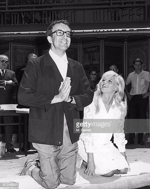 3rd June 1964 British actor Peter Sellers kneels while his wife Swedish actor Britt Ekland looks on during an imprint ceremony outside Grauman's...