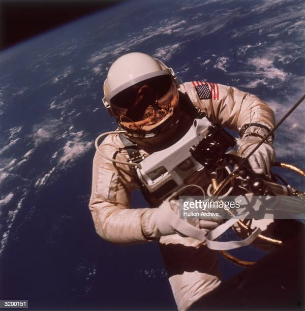 Gemini IV astronaut Edward White II performing the first EVA in space June 3 1965 He is holding a HandHeld SelfManeuvering Unit which enables him to...