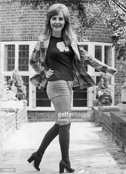 Pop singer Lulu poses in hotpants and kneelength boots in the garden of her Hornsey home London