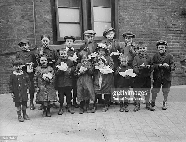 Children eating a penny's worth of Plum Duff from soup kitchens in Bermondsey south London
