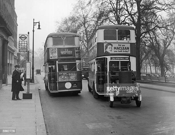 A gas producer bus passes a petrol driven bus on London's Park Lane during a tests to compare the efficiency of the new fuel source