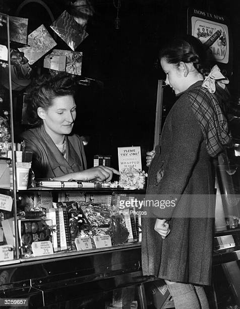 A young girl is offered to try a sample of a sweet before buying at Paddington Station in London