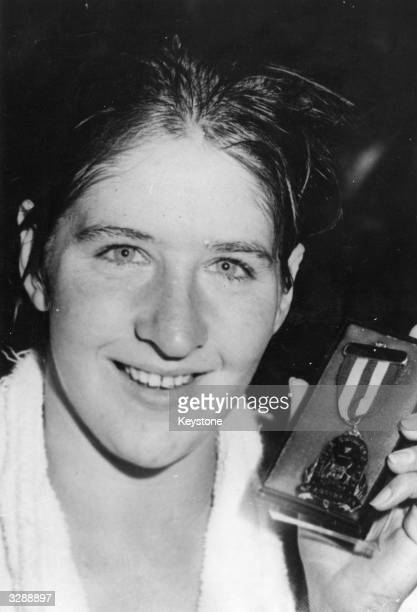 Australian swimmer Dawn Fraser holding her victory medal after her performance in the Australian Swimming Championships at which she broke 5 of her...