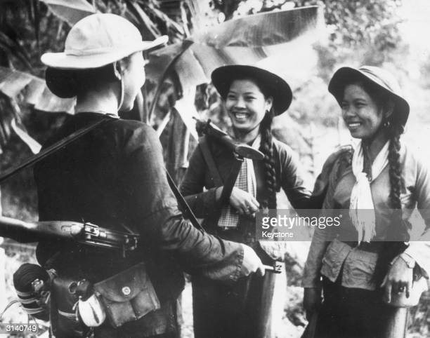 Three young women from South Vietnam with rifles on their shoulders