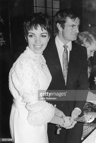 American actor and singer Liza Minnelli wearing a white lace bridal gown smiling and cutting her wedding cake with her first husband Peter Allen