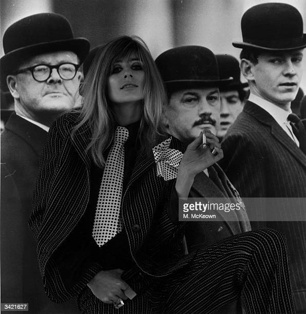 Model Jill Kennington in rebellious mood as she poses in a man's suit against a backdrop of men in suits and bowler hats